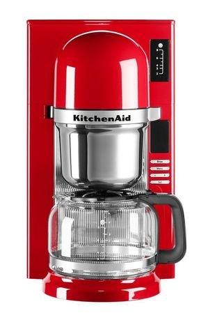 Кофеварка заливного типа, графин (1.18 л), краснаяКофемашины<br>Современная кофе-машина от Kitchenaid варит несравненный кофе, будто интуитивно выбирая необходимую температуру, подстраиваясь под степень обжарки зерен. Все дело - в инновационной системе заваривания пуровер - pourovercoffee, наиболее близкой к ручному приготовлению ароматного напитка.     В отличие от капельной технологии, при которой вода пропитывает засыпанный в конус молотый кофе, после чего кофе по капле поступает в графин, пуровер обеспечивает подачу горячей воды на кофе непрерывной струйкой. Впитывая воду, молотый кофе выделяет углекислый газ, от чего вкус получается более ярким и насыщенным.     Резервуар для воды расположен непосредственно над сеткой для кофе. Вода, нагретая до температуры 93&amp;deg;С, способствует полному раскрытию вкуса и аромата кофе.<br><br>Серия: Капельная кофеварка KitchenAid