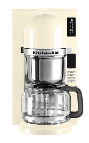 Кофеварка заливного типа, графин (1.18 л), кремоваяКофемашины<br>Современная кофе-машина от Kitchenaid варит несравненный кофе, будто интуитивно выбирая необходимую температуру, подстраиваясь под степень обжарки зерен. Все дело - в инновационной системе заваривания пуровер - pourovercoffee, наиболее близкой к ручному приготовлению ароматного напитка.     В отличие от капельной технологии, при которой вода пропитывает засыпанный в конус молотый кофе, после чего кофе по капле поступает в графин, пуровер обеспечивает подачу горячей воды на кофе непрерывной струйкой. Впитывая воду, молотый кофе выделяет углекислый газ, от чего вкус получается более ярким и насыщенным.     Резервуар для воды расположен непосредственно над сеткой для кофе. Вода, нагретая до температуры 93&amp;deg;С, способствует полному раскрытию вкуса и аромата кофе.<br><br>Серия: Капельная кофеварка KitchenAid