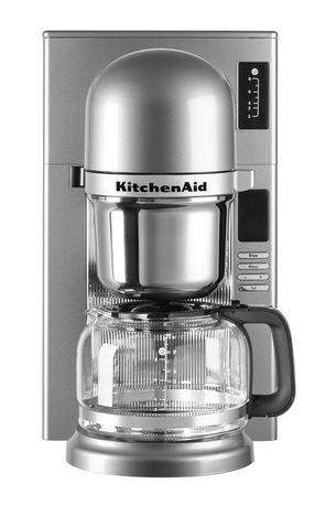 Кофеварка заливного типа, графин (1.18 л), серебристаяКофемашины<br>Современная кофе-машина от Kitchenaid варит несравненный кофе, будто интуитивно выбирая необходимую температуру, подстраиваясь под степень обжарки зерен. Все дело - в инновационной системе заваривания пуровер - pourovercoffee, наиболее близкой к ручному приготовлению ароматного напитка.     В отличие от капельной технологии, при которой вода пропитывает засыпанный в конус молотый кофе, после чего кофе по капле поступает в графин, пуровер обеспечивает подачу горячей воды на кофе непрерывной струйкой. Впитывая воду, молотый кофе выделяет углекислый газ, от чего вкус получается более ярким и насыщенным.     Резервуар для воды расположен непосредственно над сеткой для кофе. Вода, нагретая до температуры 93&amp;deg;С, способствует полному раскрытию вкуса и аромата кофе.<br><br>Серия: Капельная кофеварка KitchenAid