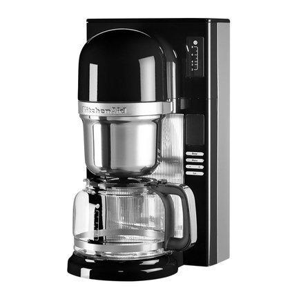 Кофеварка заливного типа, графин (1.18 л), чернаяКофемашины<br>Современная кофе-машина от Kitchenaid варит несравненный кофе, будто интуитивно выбирая необходимую температуру, подстраиваясь под степень обжарки зерен. Все дело - в инновационной системе заваривания пуровер - pourovercoffee, наиболее близкой к ручному приготовлению ароматного напитка.     В отличие от капельной технологии, при которой вода пропитывает засыпанный в конус молотый кофе, после чего кофе по капле поступает в графин, пуровер обеспечивает подачу горячей воды на кофе непрерывной струйкой. Впитывая воду, молотый кофе выделяет углекислый газ, от чего вкус получается более ярким и насыщенным.     Резервуар для воды расположен непосредственно над сеткой для кофе. Вода, нагретая до температуры 93&amp;deg;С, способствует полному раскрытию вкуса и аромата кофе.<br><br>Серия: Капельная кофеварка KitchenAid